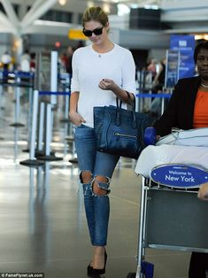Simple accessories: Kate Upton carried a stylish leather handbag and shielded her eyes with black sunglasses as she made her way out the airport