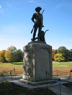 Bronze Blue Minute Man at Concord Bridge in a blue sky.