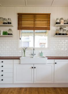 "tiles Farmhouse A tastefully renovated kitchen in a traditional ""Queenslander"" Home in Queensland, Australia. Complete with a farmhouse sink, subway tile on the walls, butcher block counter tops, and open shelving - this kitchen is sure to inspire! White Farmhouse Kitchens, Farmhouse Sink Kitchen, Country Kitchen, New Kitchen, Home Kitchens, Farmhouse Layout, Kitchen With Window, Wooden Kitchen Bench, Small Kitchen Redo"