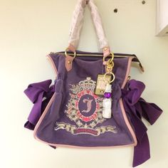 Juicy Couture Handbag Purple/Pink •posh velour texture w/ patterned leather trim •the luxe crest embroidery & drawstring detailsturdy twin handles & spacious interior ensure it is still practical enough to hold all of your necessities this season. •Made of plush velour fabric with leather trim. Dual shoulder straps. •Intricate Juicy crest embroidered pattern detailing on the front. •Cinched drawstring detail with a ribbon bow accent. •Flat bottom. •Holds your wallet, sunglasses, phone, a…