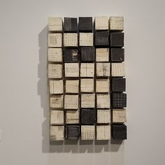 A Rectangle of Cubes by Lori Katz. Cubes are slab-built and extruded stoneware with slips and underglaze. Each cube hangs from a screw inserted into a hole on its back. Each grouping is unique with cubes in a variety of marks and patterning. A hanging template is included. Dimensions are for grouping as shown.