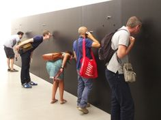 Biennale Architettura 2012, Brasil.Visitors peep into a house designed by Kogan's Studio mk27 that was filmed by Lea Van Steen. Watching people look into the peepholes, many of which require some effort, is as interesting as these filmed voyeuristic glances inside the house.