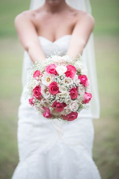 Red and white wedding bouquet with roses and baby's breath.