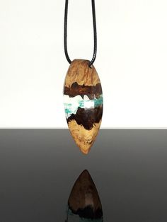 Exotic necklace. Crystal clear resin with blue swirls and wood pendant. Handmade jewelry by WoodAllGood. #WoodAllGood