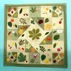 "Lap Quilt - 15. Leaves by Susan Skornia. From Susan: ""My own design fits the leaves I found in Tallahassee and Michigan, my birth state. After creating patterns from them, I marked matching fabric, embroidered the veins, cut out the leaves, and appliqued each one onto a block. Fruit and flowers added more color. Diane Higginbotham's leaf quilt was my inspiration."""