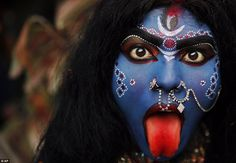 Colourful: A woman elaborately made up to look like the Hindu goddess Kali joins the procession in the Indian city of Allahbad