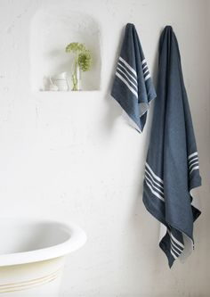 6b05615672 Loaf s navy blue Hammam towels with simple stripes hung above a roll top  bath in this