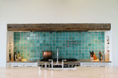 turquoise tile backsplash with rustic beam