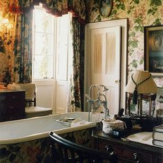 Floral wallpaper with matching curtains gives a Victorian-style look to this ensuite bathroom. The floral design continues on the freestanding bath. An antique desk and chair and wall sconces add to the country house scheme.