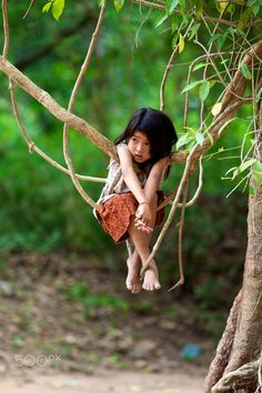 A Khmer Child hangs on the jungle vines outside Ta Prohm Temple in Angkor, Cambodia