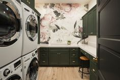 A black door opens to a charming pink and black laundry room equipped with 2 sets of white front loading washer and dryers and boasting a pink and black rose wallpaper clad accent wall.