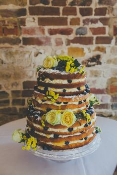 Naked sponge wedding cake with yellow flowers & blueberry decor - Image by Dale Weeks Photography - La Sposa Lace Wedding Dress with Pink Bridesmaid Gowns from ASOS & a Bespoke Grooms Suit for a classic wedding in a barn with Naked Cake & fabric petal backdrop decor.