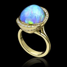 Tulip Opal Ring by Adam Neeley.  Tulip Ring is bold and  enchanting. This ring design features a stunning 9.85 carat Ethiopian  opal complemented by .55 carats total weight or diamond pavé, all set in 14 karat yellow gold.