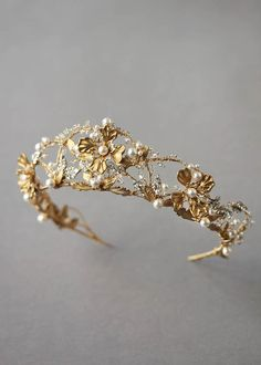 A hypnotic beauty, the Reina gold pearl wedding crown is an opulent and feminine piece. Rich in textured botanical detailing, its gold sculptural blooms are set onto delicate beading details.
