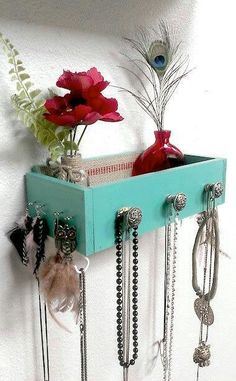 Shelf on wall for storage. Cool use of knobs for jewelry, can be used for keys and wallet