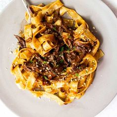 Short ribs braised with mushrooms and red wine until they're falling apart tender. Serve the sauce with pappardelle pasta for a rich and decadent cold-weather dinner. #shortribs #pasta #mushrooms