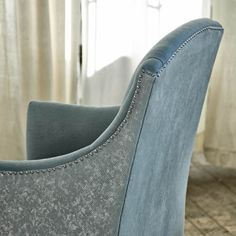 Upholstered chair with leather sides and nail head detail