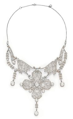A BELLE EPOQUE DIAMOND NECKLACE - The front suspending an openwork old mine, old European and rose-cut diamond foliate plaque, the central flower blossom set at the center and corners with larger old European-cut diamonds, suspending three articulated old mine-cut diamond pendants, to the fine link backchain, mounted in platinum-topped gold, circa 1890