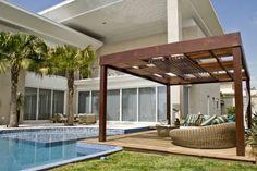 Projeto assinado por Claudia Canales com estrutura de pergolado em madeira, integrado à area da piscina