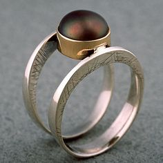 Ring by Timmer Designs. Two hand forged hoops of sterling silver cradle a pearl held by a 14k gold bezel.