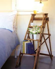 Stepladder Bed Stand  Take advantage of every bit of bedroom space by stacking your nighttime necessities instead of crowding them on top of a tiny stand. The four wide rungs of an extra stepladder provide a steady spot for a row of books as well as the necessary alarm clock and reading lamp.