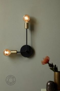 Minimalism meets Scandinavian design. This stunning wall light features brushed brass and matte black metal. Two beautiful naked globes create a warm glow onto its surrounding environment. #minimalism #scandinavian #design #nordic #design #lighting #lightingdesign #metal #wallights #scandinavianwallights #nordicwallights #nordiclighting #scandinavianlighting #bedroomlighting #bedroom #livingroom #decor