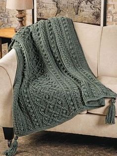 This crochet blanket features cables that both run the length of the pattern and also weave in and around each other