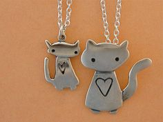 """Mother Daughter Space Kitties from marmar.  This is a sweet matching set for a mother and her daughter to wear to the family picnic! Made from sterling silver it is two necklaces, the mother is 1 1/8"""" tall, the daughter is 3/4"""" tall. The """"baby"""" hangs from a 16"""" silver-plated cable chain and the """"mom"""" hangs from an 18"""" silver-plated cable chain.   $58.00"""