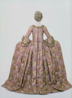 Woman's court dress and petticoat (Robe a la Francaise Italian 1776 Lilac ground with a brocaded design of waving lines, and of white silk and gold thread, and bunches of flowers woven with bright colored silks and silver and gold thread. The over-dress hangs from the shoulders in two box-plaits, and is trimmed with gold lace and rosettes of ribbon and silk suggesting flowers. The under-dress consists of an apron, arranged so as to give the effect of an under skirt.