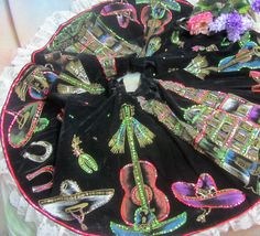 """It features Spanish guitars, spurs and Mexican hats, on both sides is a painting of a cathedral with """"San Juan de los Lagos"""" written on it. The skit has an old metal zipper in working order. The hem has a lovely white lace edge, it is a woven net with a floral pattern and re embroidery top stitch. 