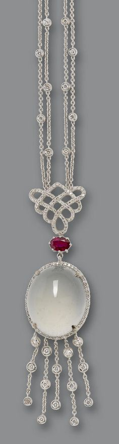 A jadeite, ruby, and diamond necklace The central oval jadeite cabochon, of near colourless material and glass-like translucency, within a brilliant-cut diamond surround, surmounted by an oval-cut ruby and brilliant-cut diamond Chinese knot motif, terminating in a fringe of collet-set diamonds, suspended from a diamond-set double chain necklace, mounted in 18k white gold, diamonds approximately 2.00 carats total, necklace length 40.5cm.