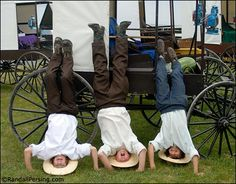 Amish children having fun while doing hand stands..