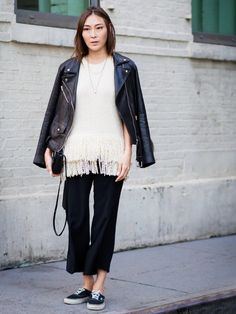 Jayne Min wears a knit fringe top, cropped pants, a draped leather jacket, black bag, and Vans sneakers