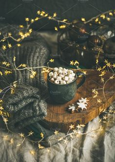 #Christmas winter hot chocolate Christmas or New Year winter hot chocolate with marshmallows and cookies in black mug over wooden board served in bed with holiday light garland blanket and gray sweater selective focus copy space