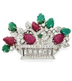 ART DECO EMERALDS, RUBIES AND DIAMONDS PIN Depicting a basket of flowers set with baguette diamonds, marquise and half size, flowers adorned with emeralds and rubies engraved platinum setting, gross weight. 16.70 gr, 1930