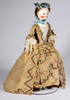 English pandora of turned, carved and jointed wood, 1755-1760. Pandoras were used from the 14th century to convey the latest fashions among the courts of Europe. This wooden figure is dressed in a silk sack back robe with matching petticoat and stomacher. She wears all the accessories and underpinnings of a fashionable lady of the late 1750s.