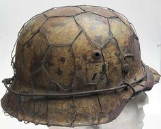 This refurbished genuine helmet shell & reproduction parts helmet is based on the Italian campaign of World War Two as used by the Waffen SS.  The shell is 100% genuine, the rest of the parts are reproduction and aged to look 70+ years old.  It has a RAL7009 base and Italian Campaign camo tan paint finish. The decal is museum quality and the camo paint is from the 1950's stock.  The decal is museum quality second ss pattern version and is carefully blended into the helmet. www.warhats.com
