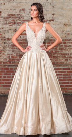 Beaded appliques over metallic lace adorn the bodice of this V-neck ball gown to the basque waistline. This royal look is completed with an illusion V-back, Silk Dupion full skirt, pockets, and a cathedral length train.