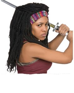 The Walking Dead Michonne Wig exclusively at Spirit Halloween - Ensure that you're safe from zombies this Halloween wearing the officially licensed Walking Dead Michonne Wig. This wig consists of long thick braids that create a voluminous head of hair. Colorful striped headband holds the hair back from your face so walkers can feel your ferocious stare from miles away. Make it yours for $19.99.