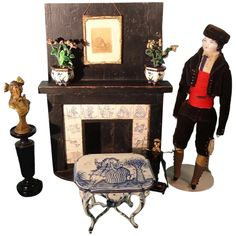 We are pleased to offer this wonderful fireplace for your consideration. It is made of wood in doll size scale and retains its original ebony surface in the hearth, mantel and back piece. Most interesting and delightful is the delft transfer plaques surrounding the hearth of cats playing instruments, frogs, fish and sailboats. Some of the transfers are torn but the blue on white transfers are most attractive against the dark wood. This is a piece never seen before since it was personally mad