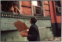 Smiling child on an open window ledge and a man below on the sidewalk holding a cigarette in one hand and a portion of a cardboard box in the other HELEN LEVITT. New York