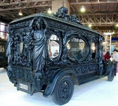 Ornate Hearse.  Wish the people directly, or reflected, in background could be taken out, along with the interior of the building this hearse is displayed in.