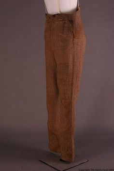 1820-1850 The trousers are made of a rust-brown ground with a medium indigo blue outlined with white windowpane check. Straight stovepipe style legs that rise high on the torso. At centerback is a waist yoke that rises from natural waist to two rounded inverted V's with japanned metal suspender buttons on each side of points. Pocket linings and waistband are lined with beige cotton. Four button broadfall with rounded corners.Two button centerfront closure.
