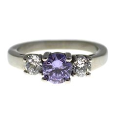 June birthstone ring or CZ fashion ring. Made from surgical stainless steel. This June birthstone ring is adorned by three beautiful CZ (cubic zirconia) stones. The center stone is a stunning 6mm lavender, Alexandrite in color, CZ stone. There are two 4mm clear side mounted CZ stones. The simulated Alexandrite and clear CZ stones sparkle in the light just like the real gemstones. This June birthstone ring has a 2.5 mm wide high polished band, available in rings size 5, 6, 7, 8, 9 or 10.