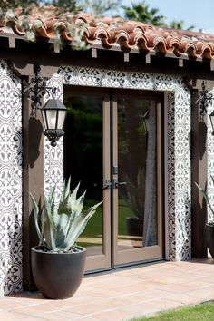 "On the exterior:  ""The client had already renovated the exterior with these beautiful black-and-white cement tiles and added pale blue-green agaves in black pots to flank the..."