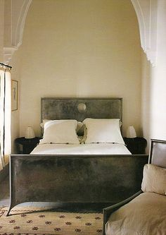 architectural detail on high ceiling and walls framing bed, creates depth, drama, coziness.