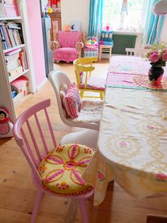 Brightly painted mismatched kitchen chairs in pink and yellow with bright granny style chair cushions.