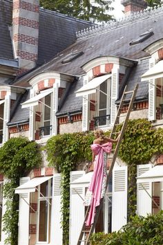 Agnès Monplaisir scales the main house at La Paillardière. Oscar de la Renta gown