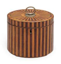 A GEORGE III FRUITWOOD AND ROSEWOOD MARQUETRY TEA CADDY   CIRCA 1790   Of oval form, the top with a brass loop ring handle   4½ in. (12 cm.) high, Christie's