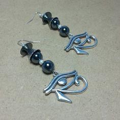 Hématites et oeil d'horus porte bonheur pour ces boucles pendentives de 6 cm , métal argenté, une lentille hématite noire,